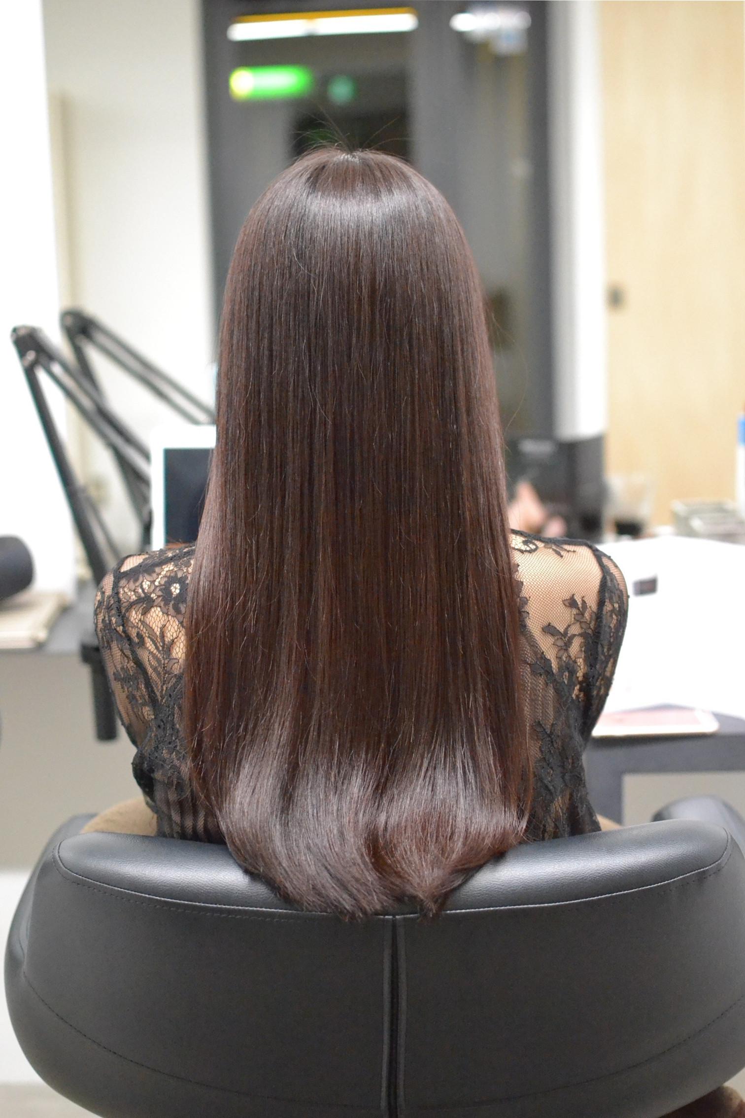 ロングヘア-で縮毛矯正をかけて髪がツヤツヤになった女性
