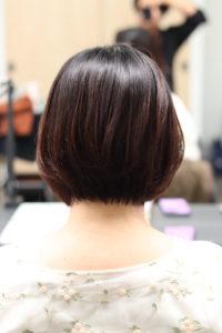 傷んだ髪が縮毛矯正でツヤツヤで綺麗にみえるようになった女性