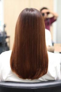 縮毛矯正で髪がまとまりツヤツヤになった女性