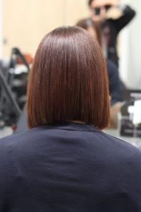 縮毛矯正で強い癖がまっすぐになった女性